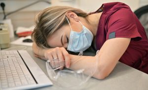 vet tech sleeping with head on desk tired from COVID